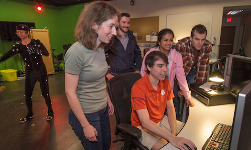 Clemson students around computer monitor